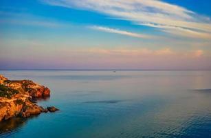 marinmålning av en stenig strandlinje vid en vattendrag med en färgglad molnig himmel foto