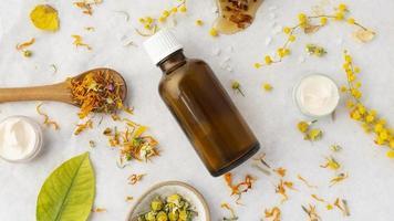 flaska med naturliga blommor, löv och ingredienser foto