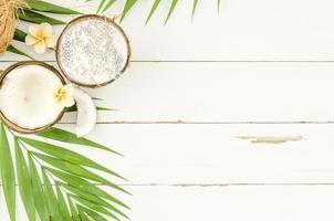 gröna palmblad med kokosnötter på träbord foto