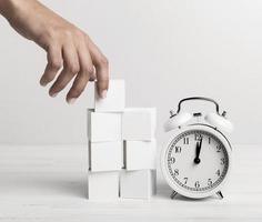 hand som sätter vita kuber bredvid klockan på vit bakgrund foto