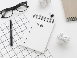 hög vinkel lista på anteckningsblock med glasögon och penna foto