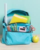blå skolväska med viktiga förnödenheter foto