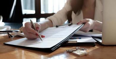 fastighetsmäklare som visar var man ska skriva under foto