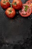 ordning av läckra färska tomater med kopieringsutrymme på svart bakgrund foto