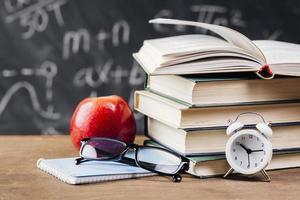 klocka och läroböcker vid lärarens skrivbord foto