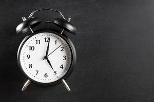 väckarklocka som visar klockan 5 mot svart bakgrund foto