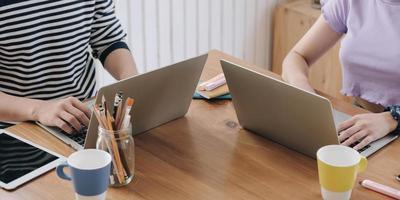 två personer som arbetar på ett bord foto
