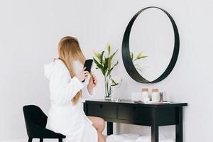 flicka tittar på hennes reflektion med hårborste foto