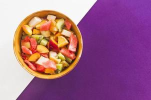 skål med fruktsallad på en vit och lila bakgrund foto