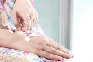 kvinna sätta lotion på händerna foto