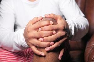 pojke som håller knä i smärta foto