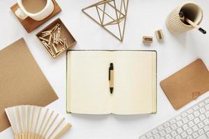 ovanifrån av neutralt skrivbord, öppen journal med penna foto