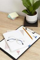 skrivbordsvy med urklipp och läsglasögon foto