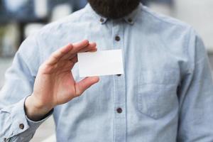 närbild affärsmans hand visar vita tomma visitkort foto