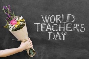 närbildhand som håller en bukett nära världslärarens svarta tavla foto