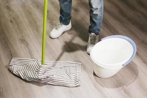 närbild man moppa golvet foto