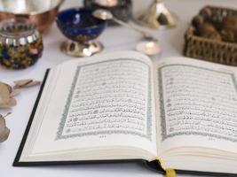 närbild öppnade koranen på bordet foto