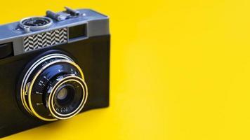 närbild vintage fotokamera med gul bakgrund foto