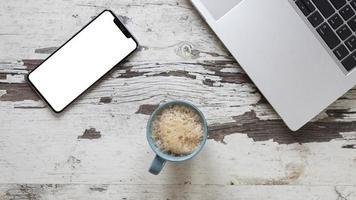 kopp kaffe på bordet med smart telefon mock up foto