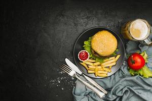 platt låg hamburgare och pommes frites på tallrik med copyspace foto