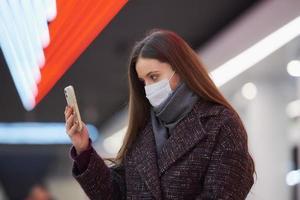 en kvinna i en medicinsk ansiktsmask väntar på ett tåg och håller en smartphone foto