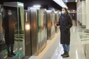 en kvinna i en medicinsk ansiktsmask väntar på ett ankommande tåg på tunnelbanan foto