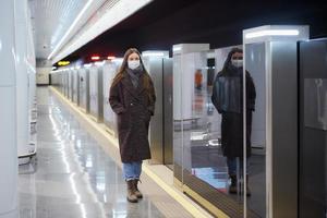 kvinna i en medicinsk ansiktsmask står nära det avgående tåget på tunnelbanan foto