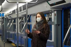 en kvinna i en ansiktsmask står och använder en smartphone i en modern tunnelbana foto
