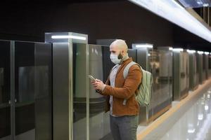 en man i ansiktsmask använder en smartphone medan han väntar på ett tunnelbanetåg foto