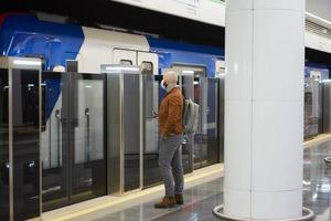 en man i ansiktsmask håller en smartphone medan han väntar på ett tunnelbanetåg foto