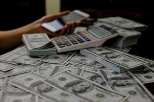 person som räknar pengar med hjälp av miniräknare foto