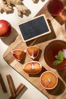 apelsiner, kombucha och digital surfplatta i köket foto