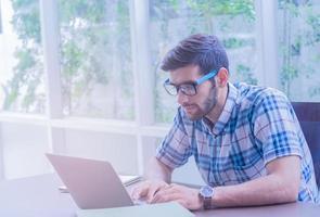 ung affärsman som hemma arbetar med en bärbar dator foto
