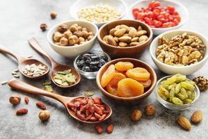 skålar med olika torkade frukter och nötter foto