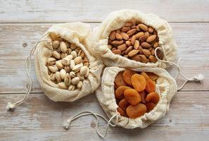 ekopåsar med pistaschmandlar, mandlar och torkade aprikoser foto