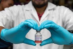 covid-19 vaccinflaska i händerna foto