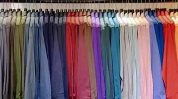 närbild av flerfärgade skjortor på galgar foto