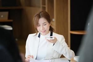 kvinna som talar i telefon medan du arbetar foto