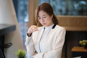 kvinna som arbetar vid ett skrivbord på ett kontor foto
