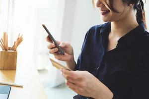 kvinna som betalar på sin telefon foto
