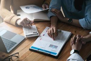 ung revisor marknadsföring team konsultera och använda en miniräknare för att analysera försäljningstillväxt på den globala arbetsplatsen marknaden. redovisningskoncept foto