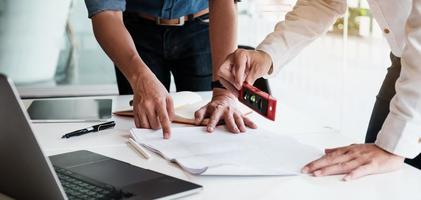 två manliga arkitekter som arbetar med en bärbar dator och ritningar för arkitektonisk plan, ingenjör som skissar ett byggprojektkoncept. foto