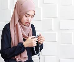 porträtt av muslimsk kvinna i traditionell klädsel med hijab och radband som ber i en moské foto