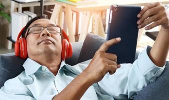 äldre asiatisk man som sitter hemma på en semester som lyssnar på musik lyckligt foto