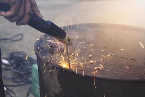 den tekniska industrins arbetare som svetsar järnstycken på jobbet med ett gnistrande ljus foto