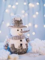 liten leksak snögubbe på vitt bord foto