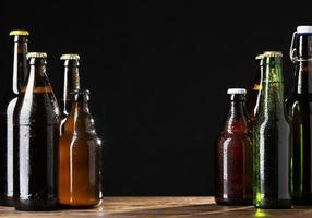 flaskor öl på svart bakgrund foto