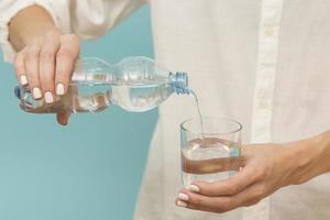 kvinna som häller vatten i glas foto