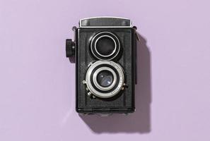 retro svart kamera på lila bakgrund foto