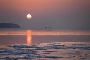 marinmålning isstrand och den röda solnedgången. foto